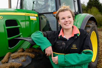 Female student alongside a Tractor